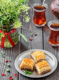 Турецкий десерт пахлава с грецкими орехами и фундуком и черный крепкий турецкий чай