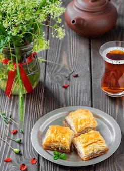Turkish dessert baklava with walnuts and hazelnuts, and black strong turkish tea