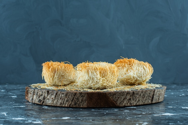 Dessert turco kadayif su una tavola, sullo sfondo blu.