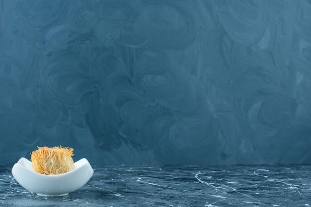 Кадаиф турецкий десерт в миске, на синем столе.