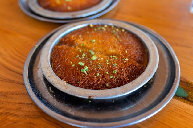 Турецкий десерт кунефе, кунафа, кадаиф с порошком фисташек и сыром, подается горячим, очень сладким.