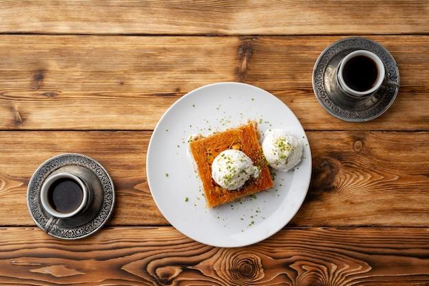 Турецкий десерт кунефе с мороженым на деревянном фоне