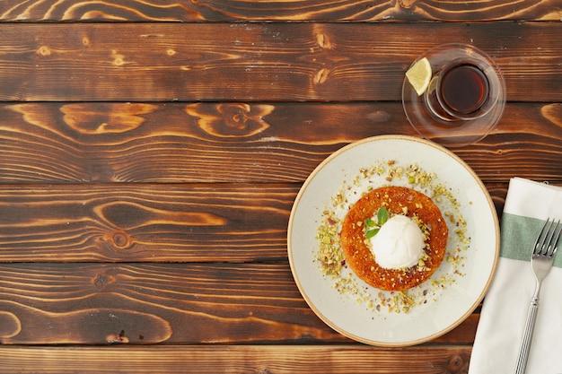 Turkish dessert kunefe with ice cream ball on wooden surface