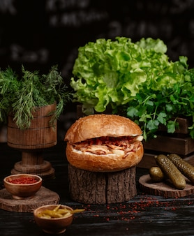 Turkish doner bun stuffed with grilled chicken and vegetables and served with turshu