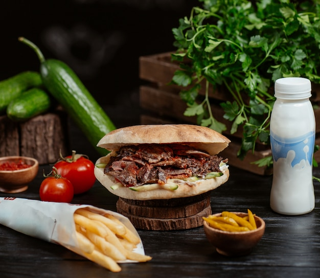 Turkish doner inside round bread with french fries and yogurt