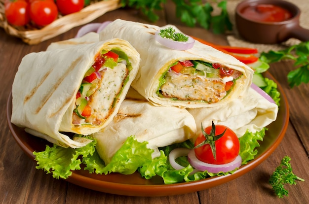Turkish doner kebab shawarma roll with meat vegetables and pita bread on a wooden