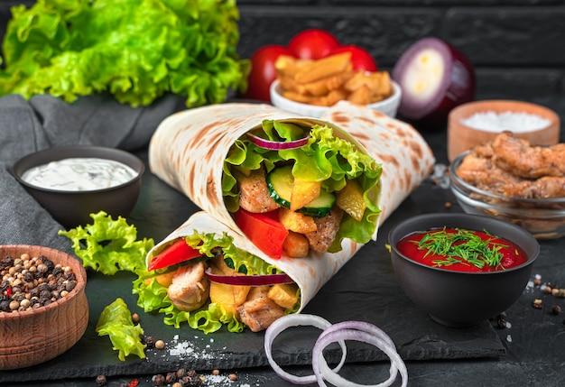 검은 벽에 구운 고기와 야채와 함께 터키 doner 케밥. 육즙이 많은 샤와 르마, 패스트 푸드. 측면보기, 클로즈업.