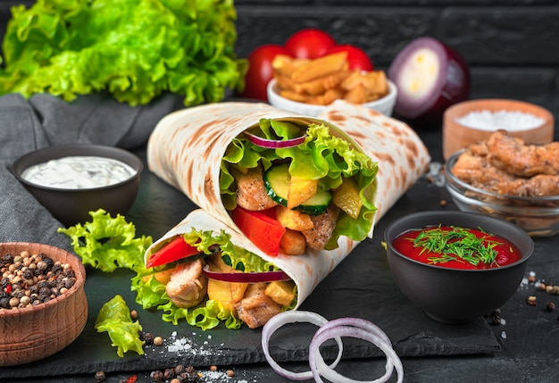 Turkish doner kebab with grilled meat and vegetables on a black wall. juicy shawarma, fast food. side view, close-up.