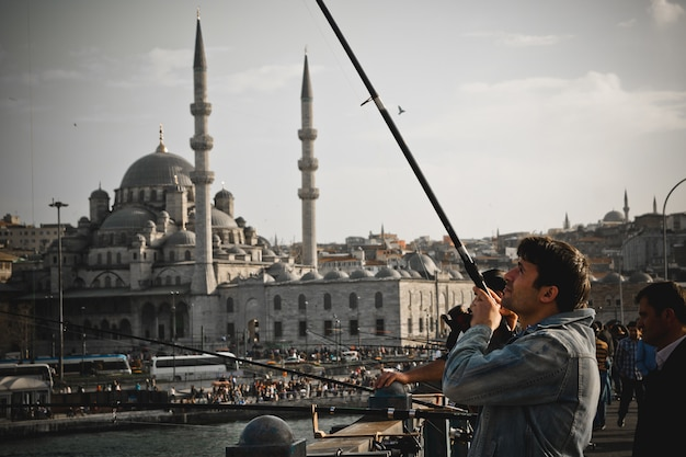 Turkish fishermen with rod on the galata bridge.