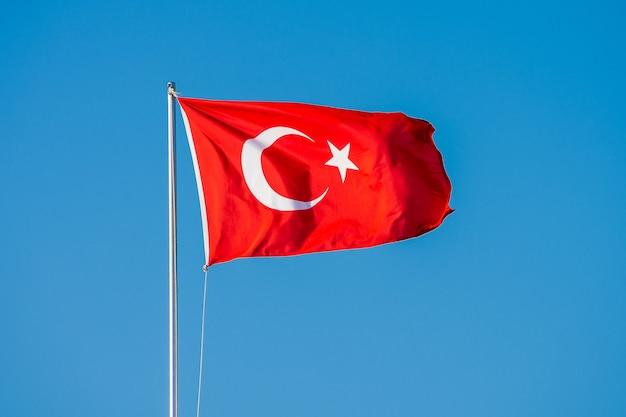 Турецкий флаг развевается на флагштоке против голубого неба. турецкий флаг развевается