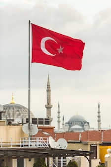 Turkish flag and istanbul rooftops view with mosque