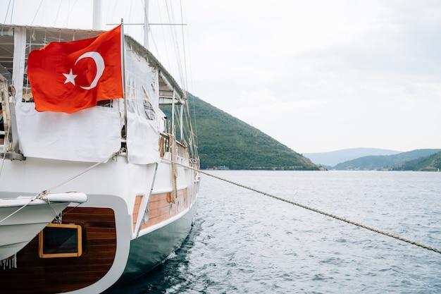 山のそばの穏やかな水の上を航行するヨットのトルコ国旗。
