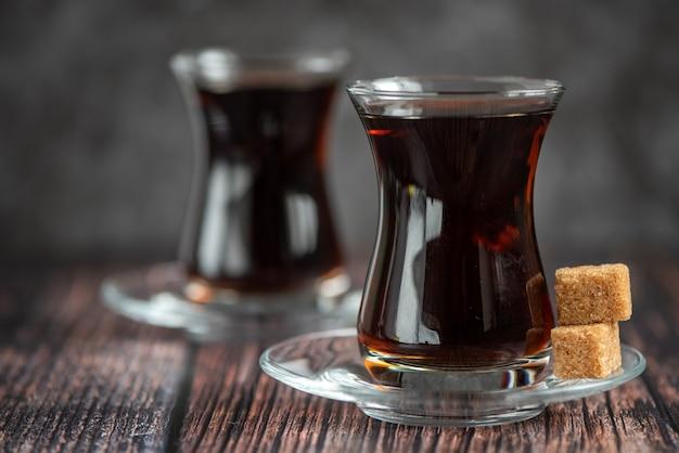 Turkish glass for tea bardak with cane sugar on dark wooden table.