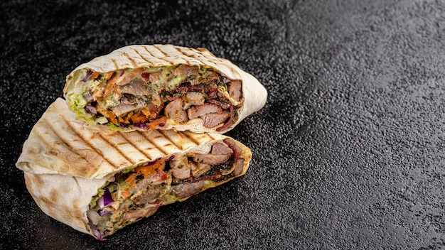 Turkish grilled kebab with lamb, tomatoes, carrots, wrapped in thin pita bread