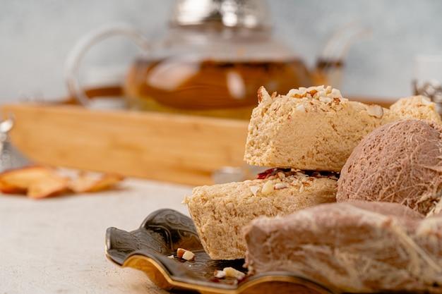 Turkish halva with tea in a glass cup close up