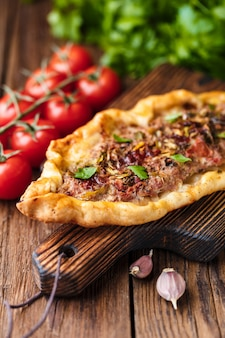 Turkish homemade pide on an rustic brown wooden table. cherry tomatoes, parsley, hot pepper, garlic are on the table.