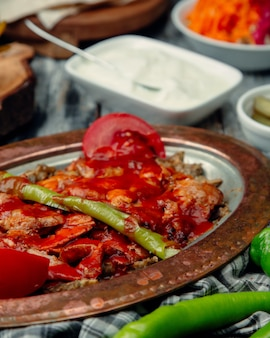 Turkish iskender kebab with tomato sauce and green chili.