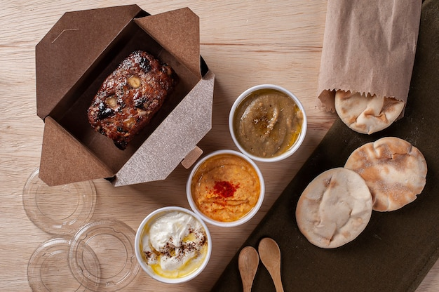 Turkish kafta, accompanied by curd, hummus and babaganoush. delivery packaging. top view