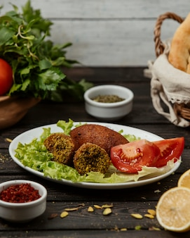 Turkish kibbeh stuffed meat balls served with tomato, and lettuce