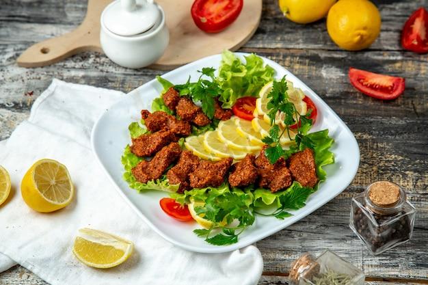 Vista laterale del limone del prezzemolo della lattuga del kofte turco