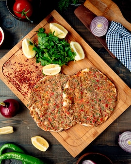 Turkish lahmacun with hot peper, parsley, and lemon slices on a wooden tray