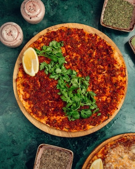 Turkish lahmacun with stuffings, lemon and chopped parsley.