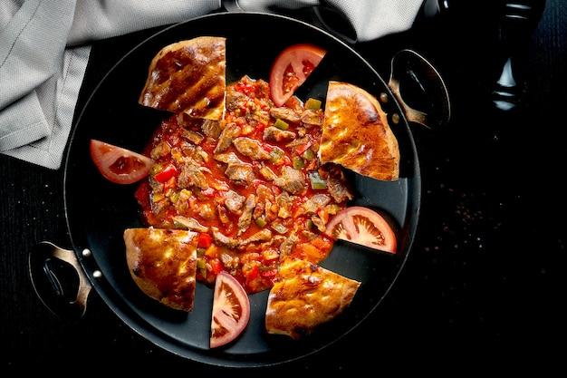 Турецкий гуляш из баранины в красном соусе с болгарским перцем и традиционными булочками в металлической посуде на черном столе. крупным планом, выборочный фокус