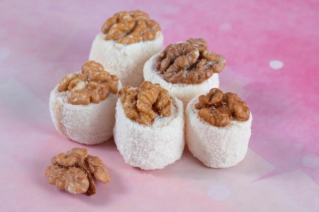 Турецкий лукум с орехом на светло-розовом фоне. фото высокого качества