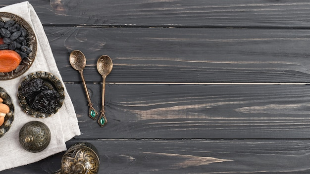 Turkish metallic spoons with dried dates; raisin over the wooden desk