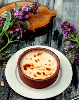 Turkish milk pudding sutlach desert in pottery bowl