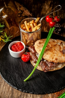 Турецкая, восточная кухня. турецкая лепешка, булочка, лаваш с кебабом и маринованным луком. обслуживание в ресторане на черном сланце, на деревянном столе