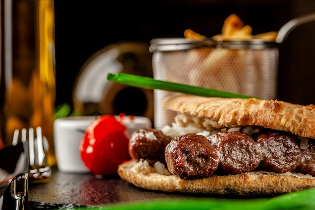 Turkish, oriental cuisine. turkish tortilla, bun, pita bread with kebab and pickled onions. serving in a restaurant on a black slate, on wooden table