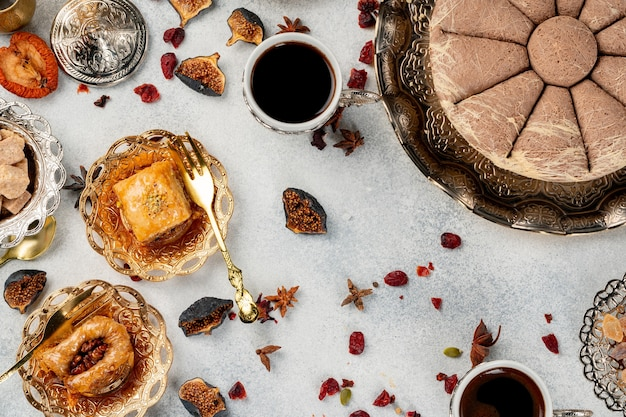 Turkish pastries and scattered dry fruits on table