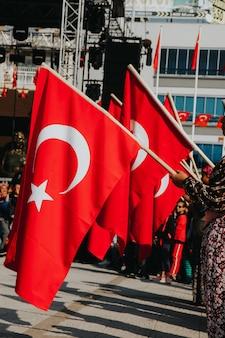 Турецкие люди держат в руках красные турецкие флаги