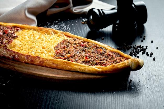 블랙 테이블에 양고기, 쇠고기 및 체다 치즈의 세 가지 충전재를 사용한 터키 피데 요리. 클로즈업, 선택적 초점