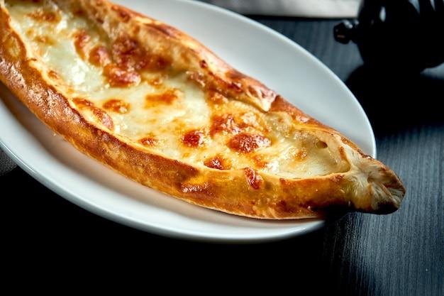 블랙 테이블에 토마토와 소금에 절인 치즈와 함께 터키 피데 요리