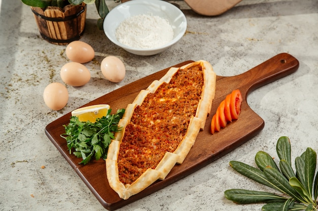 Turkish pide flatbread with minced meat and tomato topping
