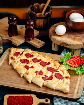Turkish pide garnished with cheese and pepperoni