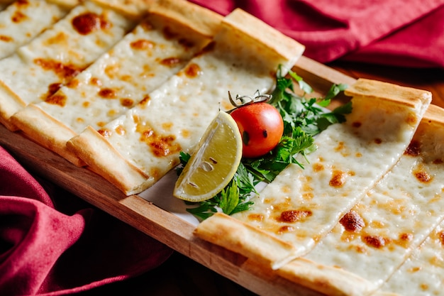 Turkish pide with melted cheese, tomato, lemon and chopped parsley.