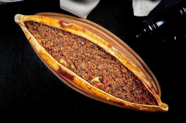다진 양고기, 토마토, 피망을 곁들인 터키 피 데가 나무 쟁반에 제공됩니다. 블랙 테이블