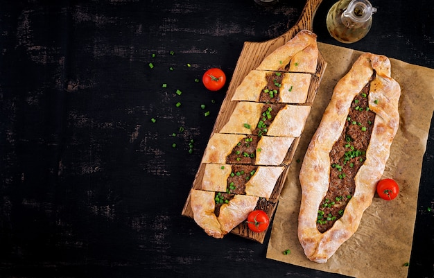 Turkish pide with minced meat, kiymali pide. traditional turkish cuisine. turkish pizza pita with meat. top view, overhead