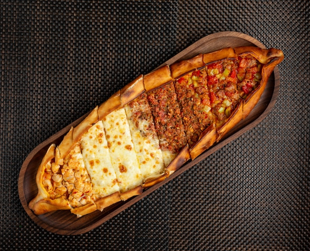 Turkish pide with stuffed meat, cheese and pieces of chicken on a wooden bowl