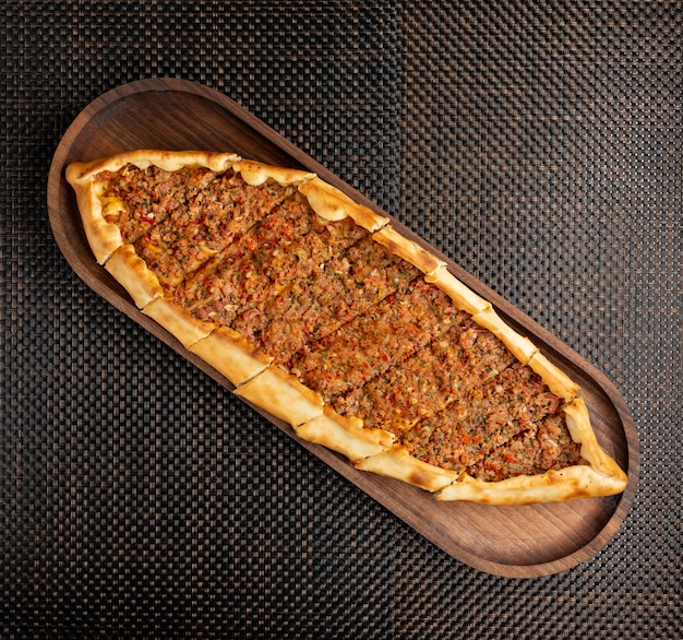 Turkish pide with stuffed meat and hot pepper on a wooden bowl