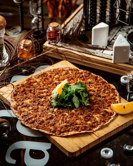 Turkish pizza lahmajun topped with parsley and lemon