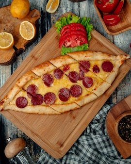 Turkish pizza pide with pepperoni , tomato and herbs.