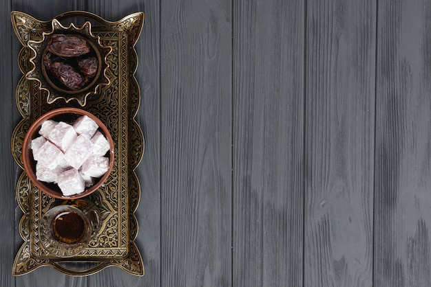 Turkish ramadan dessert lukum; tea and dates on engraved metallic tray over the black wooden surface