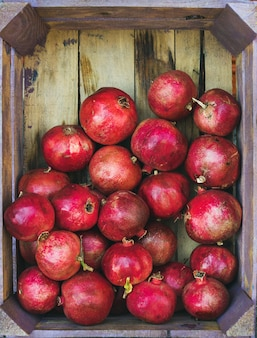Turkish ripe pomegranates in wooden box, top view