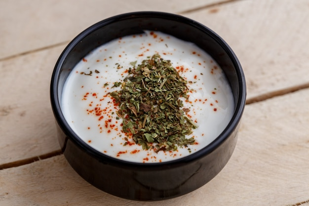 Turkish sauce of yogurt and spices in black saucer