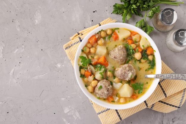 Турецкий суп с нутом, фрикадельками и овощами в белой миске на сером фоне