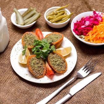Polpette di carne ripiene turche ichli kofte servite con prezzemolo e pomodoro sottaceto